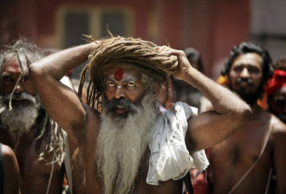 How do I look? A Hindu holy man adjusts his dreads as he waits to register for the annual pilgrimage to the Amarnath cave shrine in Jammu, India. The shrine at 3,888 meters (12,756 feet) holds an icy stalagmite representing Shiva, the Hindu god of destruction. Photo: Channi Anand, Associated Press