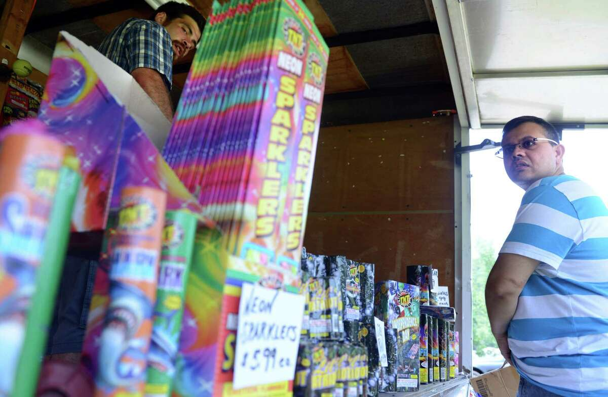 Bhushan Shah, of Seymour, stops at Patrick Raimo's road side fireworks stand to buy a few things Wednesday, July 2, 2014 near the Tri-Town Plaza in Seymour, Conn.