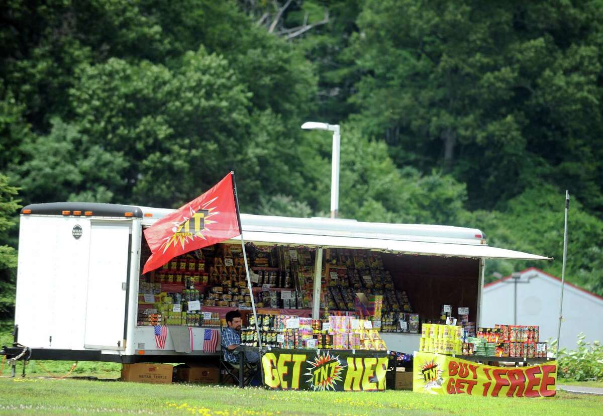 Patrick Raimo, of Naugatuck, sells fireworks Wednesday, July 2, 2014 near the Tri-Town Plaza in Seymour, Conn.