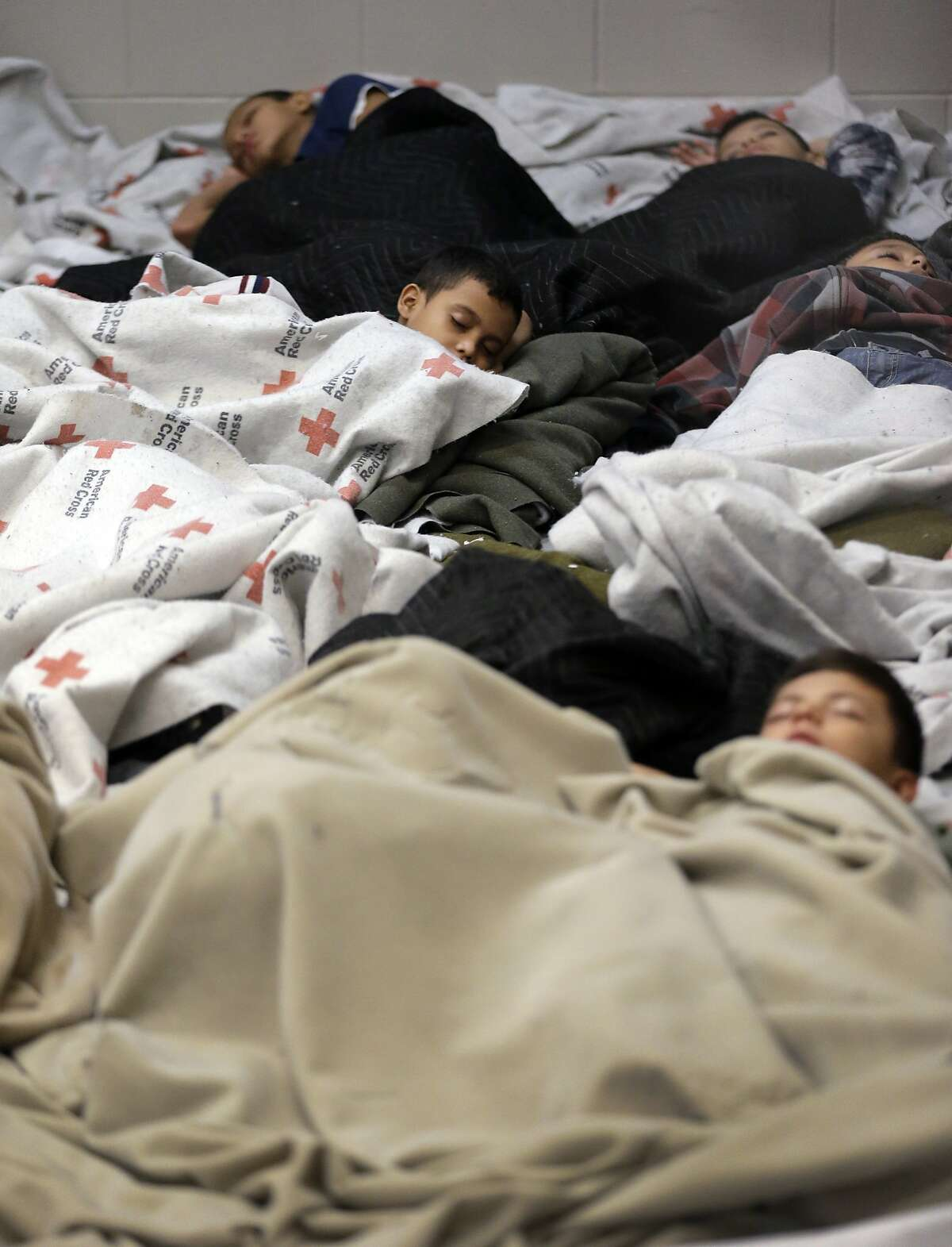 BROWNSVILLE, TX - JUNE 18: A detainees sleep in a holding cell at a U.S. Customs and Border Protection processing facility, on June 18, 2014, in Brownsville,Texas. Brownsville and Nogales, Ariz. have been central to processing the more than 47,000 unaccompanied children who have entered the country illegally since Oct. 1. (Photo by Eric Gay-Pool/Getty Images)