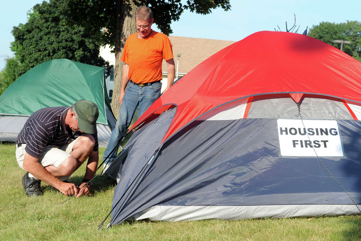 Mike Packer, left, and Paul, who chose not to give his last name, secure tents on the lawn of City Hall, in Danbury, Conn. July 1. 2014. They and others are camping in tents for a couple of weeks to protest the plight of the homeless.