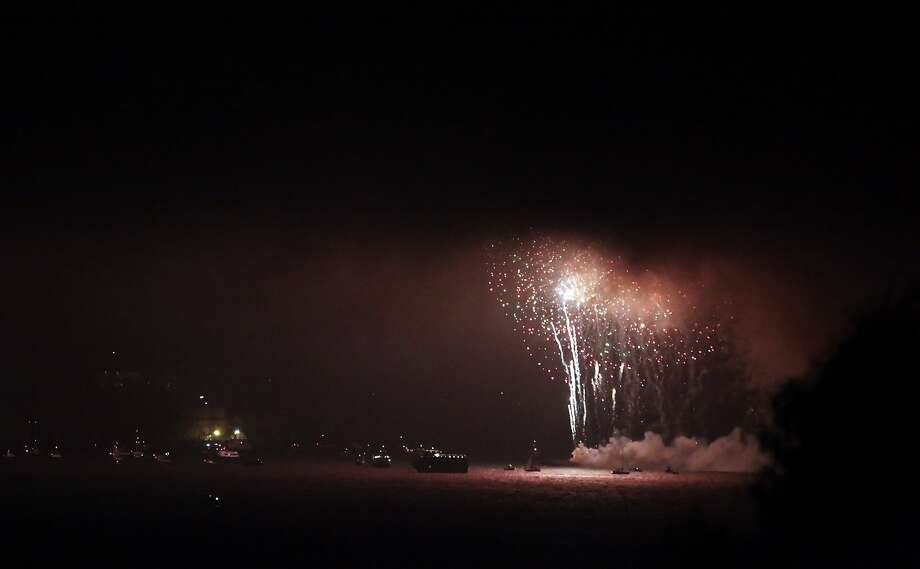 Fireworks shot from a barge on San Francisco Bay disappear into the fog over the water on a foggy Sunday night, July 4, 2010. Photo: Carlos Avila Gonzalez, The Chronicle