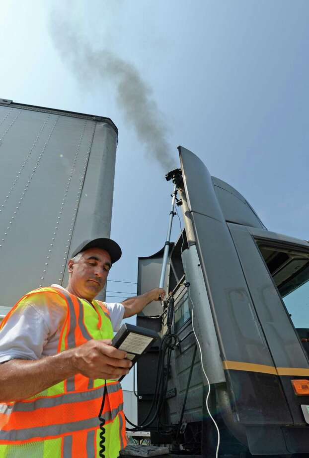 ENCON Environmental Engineer Gary J. McPherson checks the exhaust stack on a tractor for proper exhaust particulates during random testing Wednesday morning, July 2, 2014, at the Port of Albany in Albany, N.Y.  (Skip Dickstein / Times Union) Photo: SKIP DICKSTEIN / 00027607A