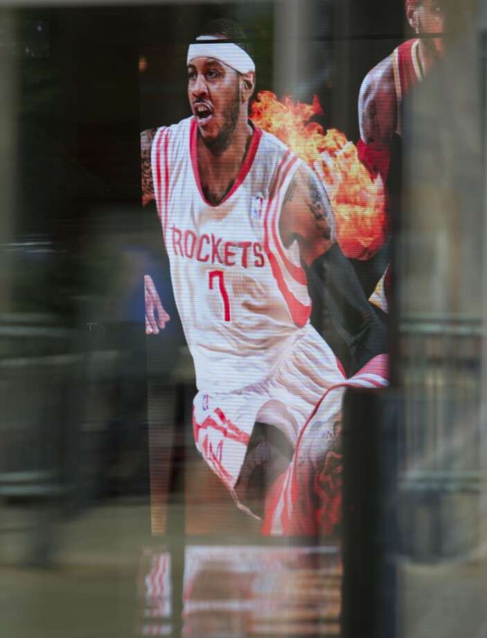 The Carmelo Anthony summer free-agent tour hit Houston today complete with a big image of him on the Toyota Center video board at center court showing him in a Rockets' jersey and wearing his No. 7. Photo: Billy Smith II, Houston Chronicle