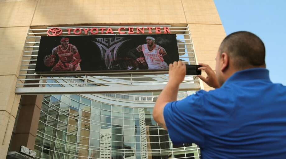 Rockets fan Frank Vasquez takes a quick photo of free agent forward Carmelo Anthony in a Rockets jersey on the Toyota Center marquee Wednesday. Photo: Billy Smith II, Houston Chronicle