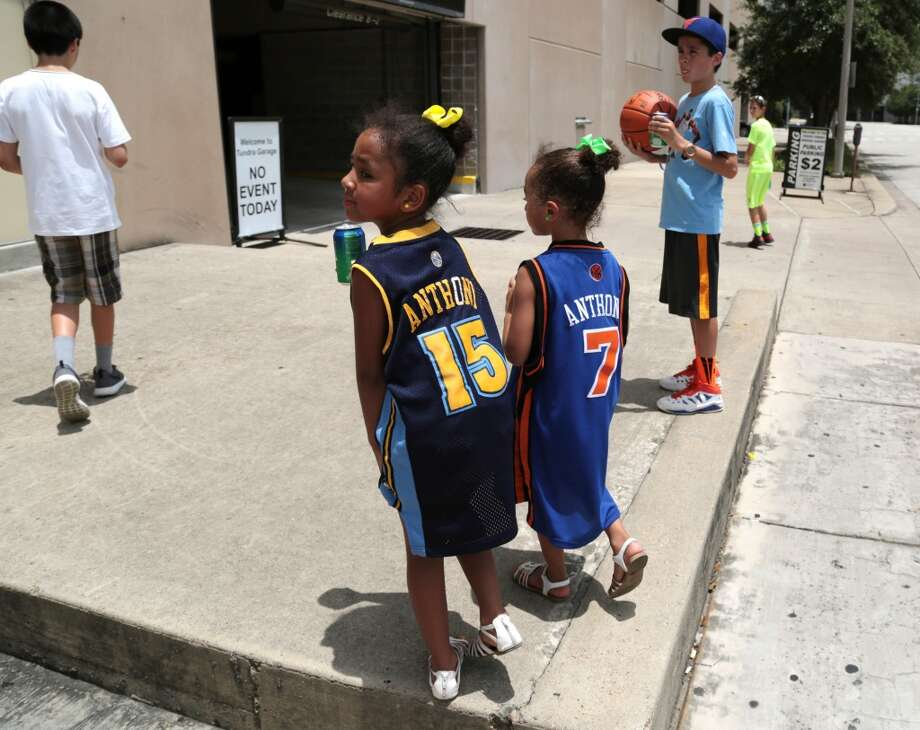 (From left) Sisters Alene Contreras and Aliyah Contreras in their Carmelo Anthony jerseys walk away disappointed from the Toyota Center without the autograph from the superstar free agent they were looking for Wednesday. Photo: Billy Smith II, Houston Chronicle