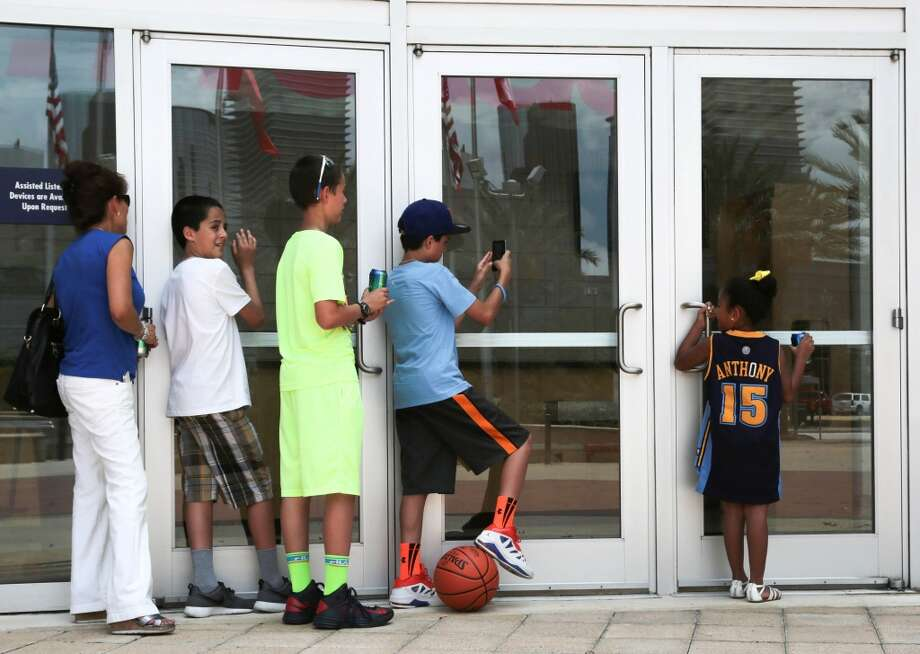 (On right) Six year-old Alene Contreras and her family peek through the windows of Toyota Center trying to catch a glimpse of free agent superstar Carmelo Anthony on Wednesday. Photo: Billy Smith II, Houston Chronicle