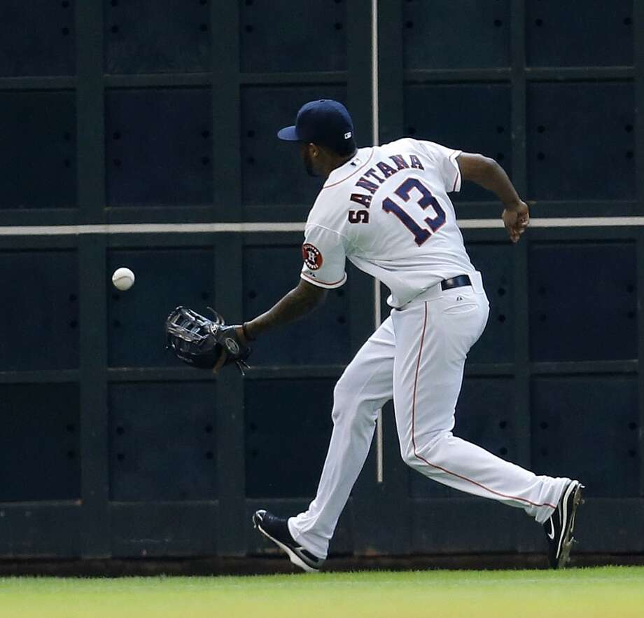 Astros left fielder Domingo Santana chases a double hit by Mariners second baseman Robinson Cano during the seventh inning. Photo: Karen Warren, Houston Chronicle