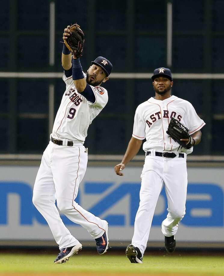 Astros shortstop Marwin Gonzalez (9) catches a pop out from Mariners second baseman Robinson Cano (22) as left fielder Domingo Santana (13) runs toward him during the ninth inning. Photo: Karen Warren, Houston Chronicle