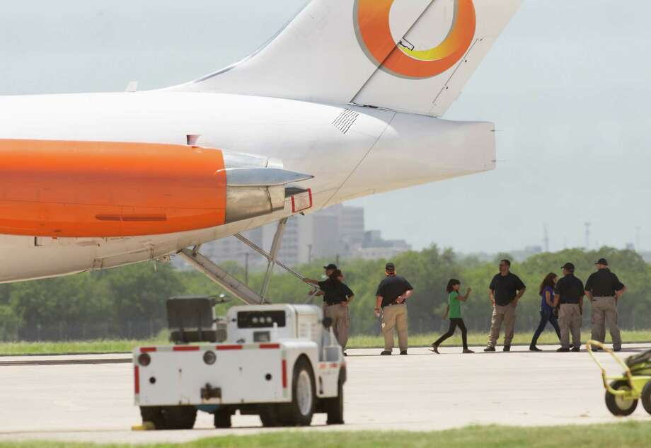 Adults direct what are believed to be undocumented minors Tuesday July 1, 2014 to buses as they get off an airplane at Port San Antonio. The plane, operated by a Orange Air, LLC arrived in San Antonio from Phoenix, Arizona according to flight records. Photo: William Luther, San Antonio Express-News / © 2014 San Antonio Express-News