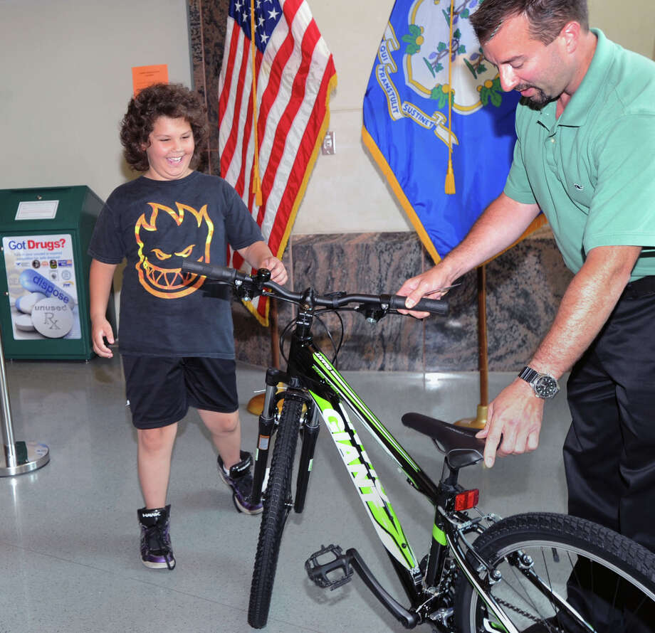 At left, Dylan Mancuso, 9, of Greenwich, smiles as he receives a bicycle from Greenwich Police Detective, Brent Reeves, at Greenwich Police Headquarters on Wednesday. Dylan's bike was stolen 2 weeks ago. Photo: Bob Luckey / Greenwich Time