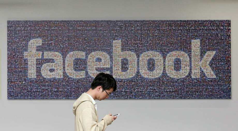 In this June 11, 2014 photo, a man walks past a Facebook sign in an office on the Facebook campus in Menlo Park, Calif. British data protection authorities said Wednesday, July 2, that it is investigating revelations that Facebook conducted a psychological experiment on its users. (AP Photo/Jeff Chiu) Photo: Jeff Chiu, STF / AP