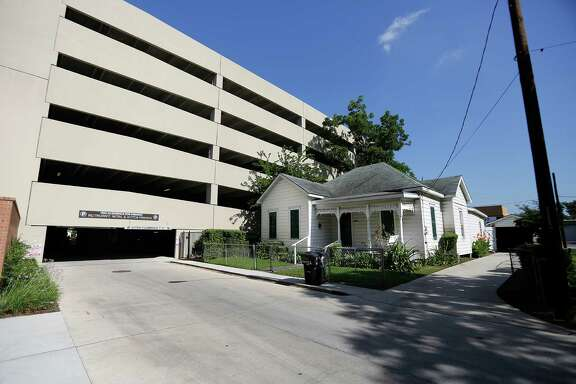 The owners of a house at 1106 O'Neil St. in Midtown now sits adjacent to a parking garage  Wednesday, June 11, 2014, in Houston.