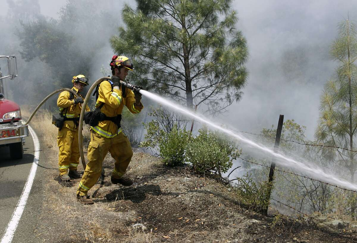 A Napa County fire crew moveis in to extinguish flames on Butts Canyon Road near Aetna Springs, Calif. on Wednesday, July 2, 2014. The Butts Fire has burned over 3,200 acres of mostly rugged terrain and destroyed as many as five buildings.