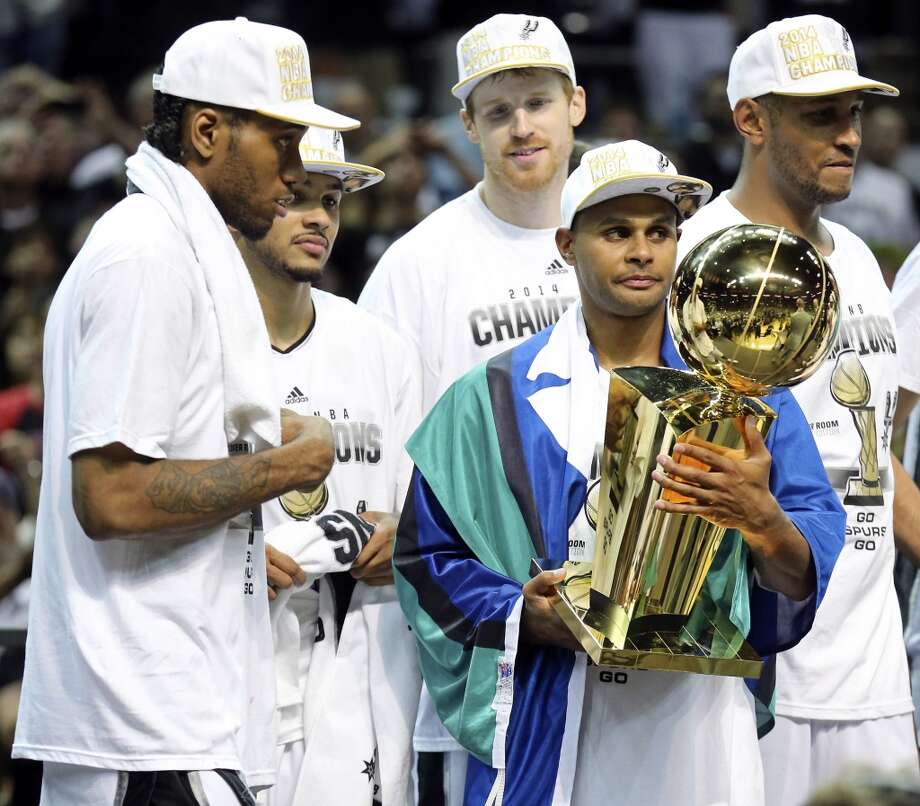 San Antonio Spurs' Patty Mills holds the trophy after Game 5 of the 2014 NBA Finals against the Miami Heat as San Antonio Spurs' Kawhi Leonard, Cory Joseph, Matt Bonner, and Boris Diaw looks on Sunday June 15, 2014 at the AT&T Center. The Spurs won 104-87. Photo: San Antonio Express-News