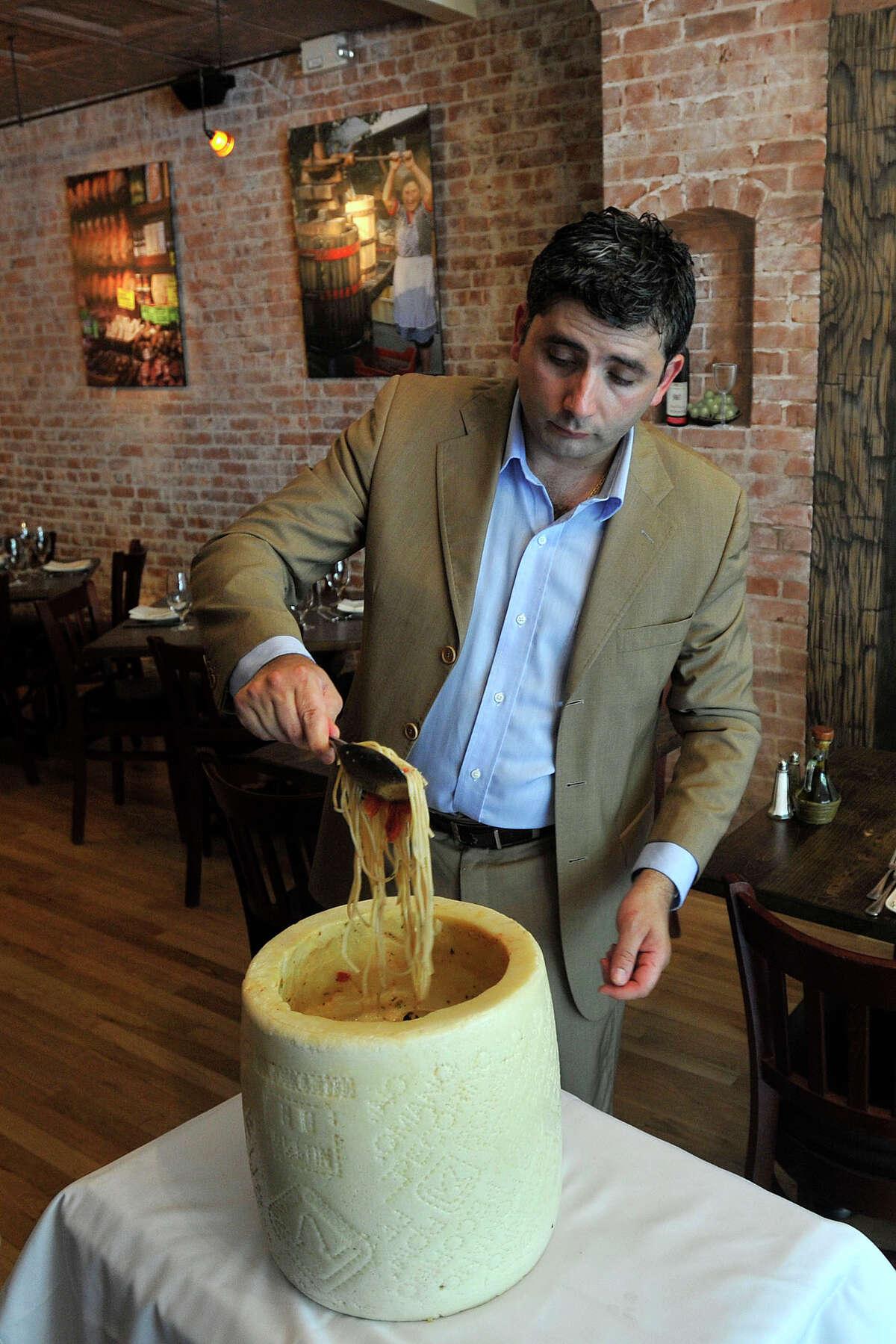 Owner Giuseppi Cinque shows off the restaurant's spaghetto alla Cinque using durum semolina pasta served in a Bambino pecorino wheel of cheese at Quartino Trattoria and Vineria in South Norwalk, Conn., on Wednesday, July 2, 2014.