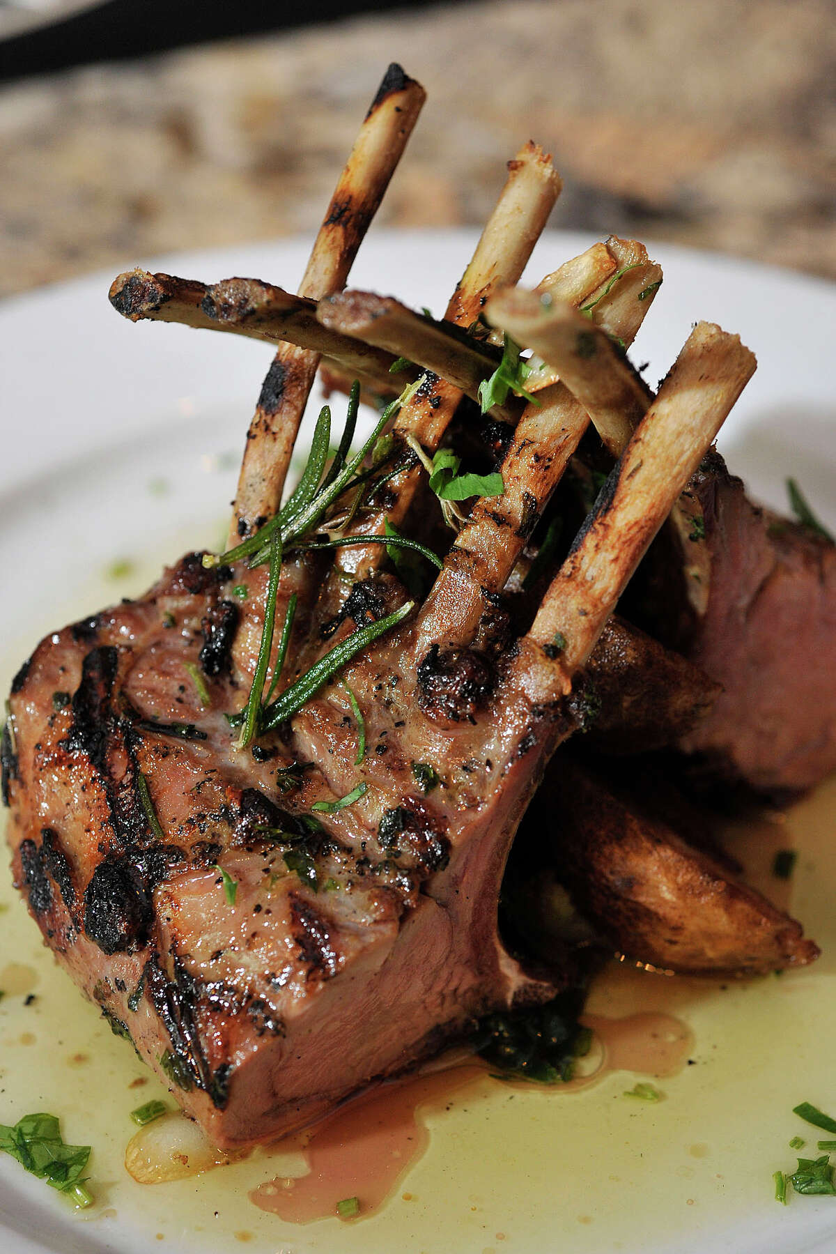 The lombatina, a grilled petit rack of veal chop with rosemary, au jus and garlic, is a featured dish at Quartino Trattoria and Vineria in South Norwalk, Conn. Photographed on Wednesday, July 2, 2014.