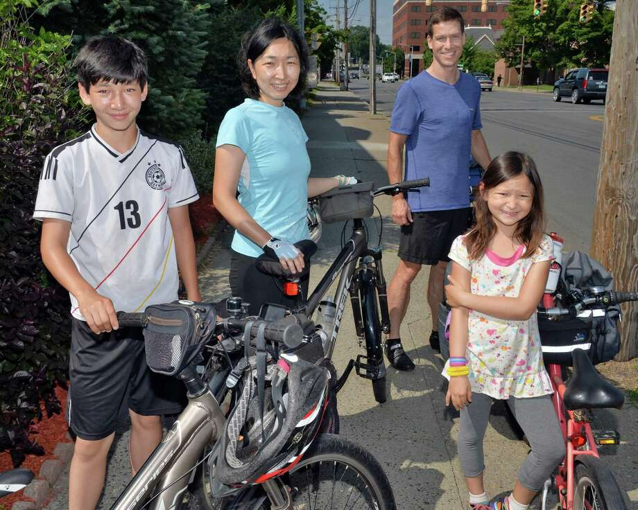 The Scott family, from left: son Sho, 13, Eiko Ikegaya, Charles and daughter Saya Scott, 7, make a stop in the Capital Region while cycling from their home in New York City to Niagara Falls and back Tuesday morning, July 1, 2014, in Schenectady, NY. They are collecting data for a roadkill project with Adventurers and Scientists for Conservation. This is their fifth family adventure, and they link each trip to charitable causes.  (John Carl D'Annibale / Times Union) Photo: John Carl D'Annibale / 00027588A