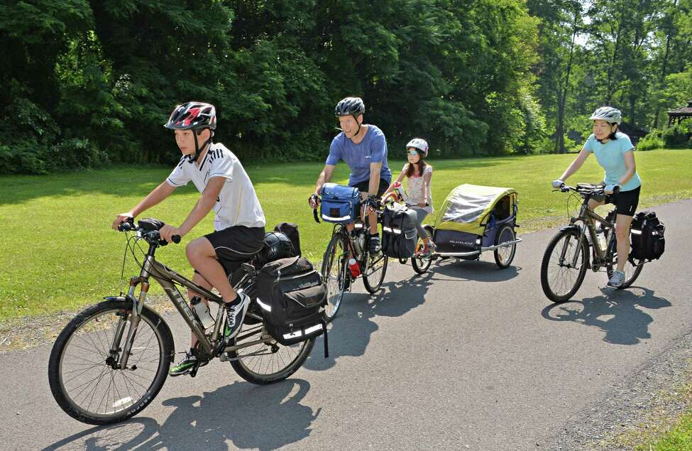 The Scott family, from left: son, Sho, 13, Charles, daughter Saya, 7, and Eiko Ikegaya, right, ride through Vale Park as they bicycle from their home in New York City to Niagara Falls and back Tuesday, July 1, 2014, in Schenectady, N.Y. They are collecting data for a roadkill project with Adventurers and Scientists for Conservation. This is their fifth family adventure, and they link each trip to charitable causes. (John Carl D'Annibale / Times Union)