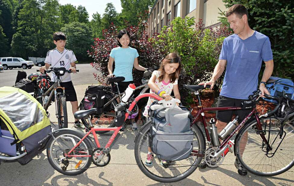 The Scott family, from left: son Sho, 13, Eiko Ikegaya, daughter Saya, 7, and Charles Scott, right, make a stop in the Capital Region while cycling from their home in New York City to Niagara Falls and back Tuesday morning, July 1, 2014, in Schenectady, NY. They are collecting data for a roadkill project with Adventurers and Scientists for Conservation. This is their fifth family adventure, and they link each trip to charitable causes. (John Carl D'Annibale / Times Union)