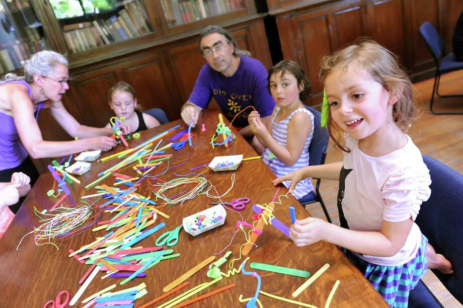 Poppy Matthews, 5, of Troy, right, joins others as they create sculptures using Popsicle sticks and pipe cleaners during an art clinic on Tuesday, July 1, 2014, at the Troy Public Library in Troy, N.Y. Skidmore College's Tang Art Museum is hosting free art clinics for children ages 5 and up at various public libraries across the region all summer. (Cindy Schultz / Times Union) Photo: Cindy Schultz / 00027582A