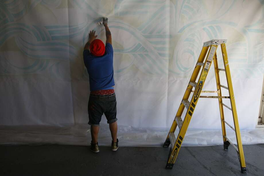 Bounce Perez works on a section of his mural. When he is done, his 26-by-22-foot banner will hang on the outside of the Yerba Buena Center for the Arts. Photo: Craig Hudson, The Chronicle