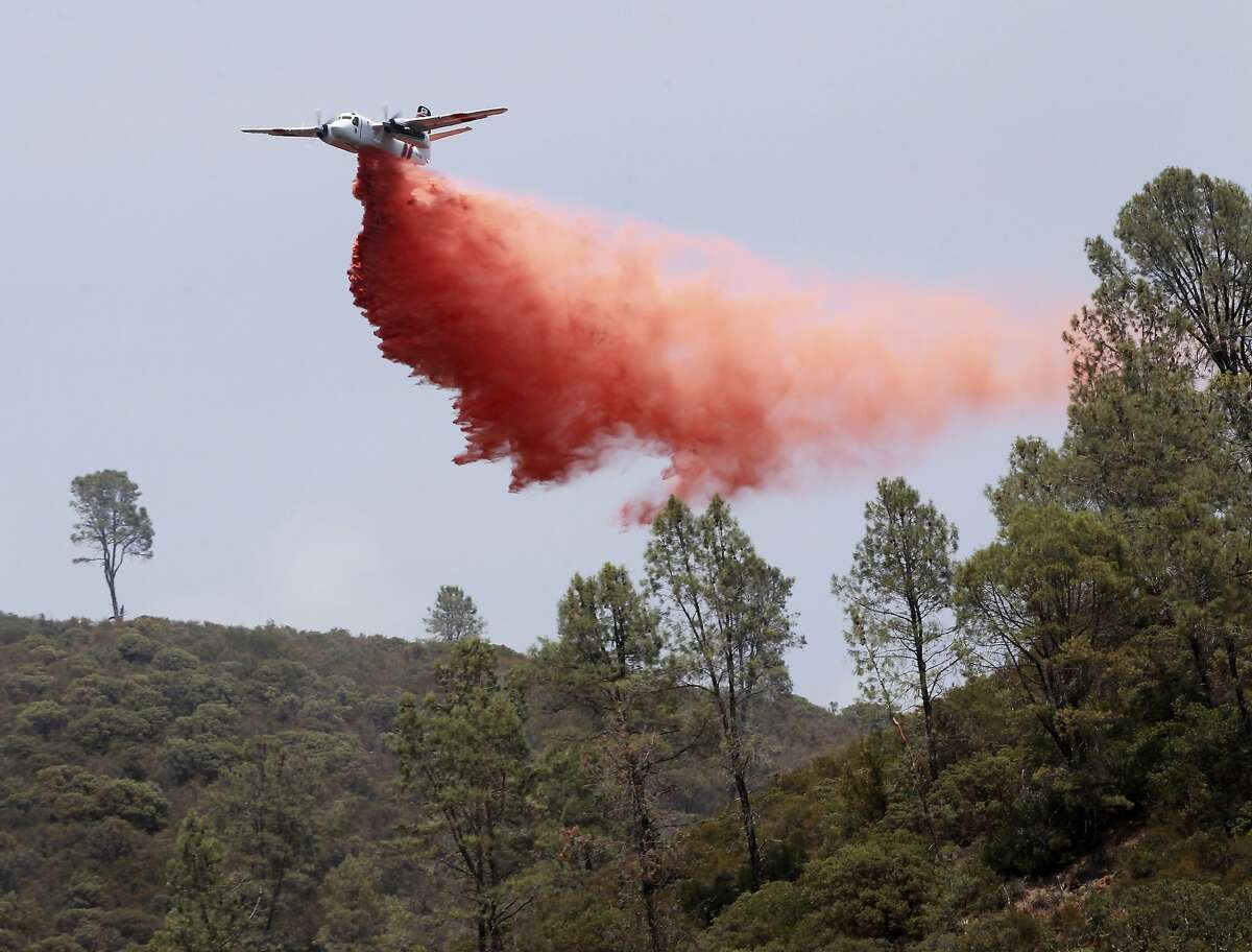 A Cal Fire air tanker drops flame retardant ahead of the fire line near Aetna Springs, Calif. on Wednesday, July 2, 2014. The Butts Fire has burned over 3,200 acres of mostly rugged terrain and destroyed as many as five buildings.