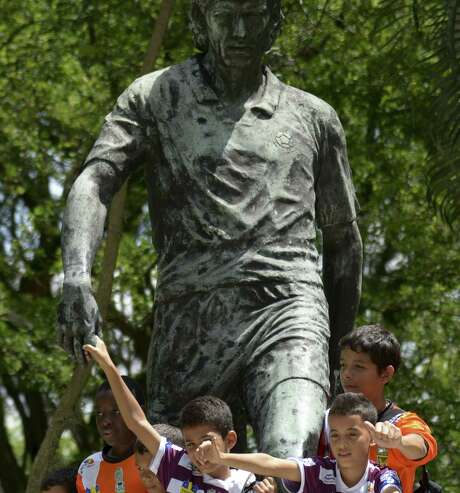 Children in Medellin pose with a statue of Colombian player Andres Escobar, who was killed after an own-goal in the 1994 World Cup. Photo: Raul Arboleda / AFP / Getty Images / AFP