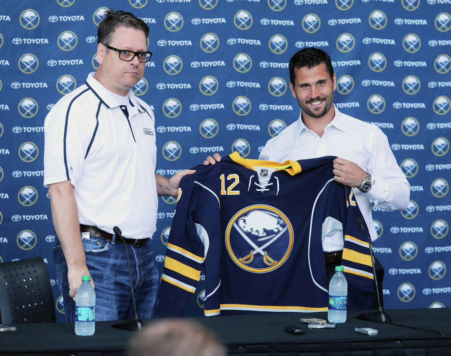 New Buffalo Sabres hockey player Brian Gionta, right, holds a Sabres jersey handed to him by General Manager Tim Murray, left, during a press conference at the First Niagara Center in Buffalo, N.Y., Wednesday, July 2, 2014. (AP Photo/The Buffalo News, Charles Lewis) TV OUT; MAGS OUT; MANDATORY CREDIT; BATAVIA DAILY NEWS OUT; DUNKIRK OBSERVER OUT; JAMESTOWN POST-JOURNAL OUT; LOCKPORT UNION-SUN JOURNAL OUT; NIAGARA GAZETTE OUT; OLEAN TIMES-HERALD OUT; SALAMANCA PRESS OUT; TONAWANDA NEWS OUT ORG XMIT: NYBUE201 Photo: Charles Lewis / The Buffalo News