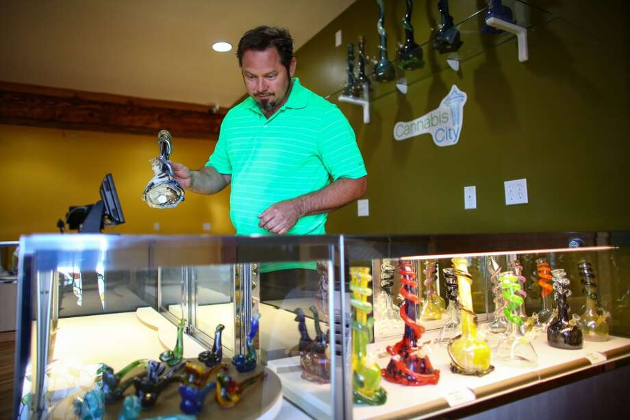 James Lathrop looks over glass at the counter of his soon-to-be state-licensed, I-502 retail store Cannabis City. The store is located in the SODO neighborhood of Seattle and is expected to be among the first 15 to 20 stores licensed on Monday, July 7, 2014, by the Liquor Control Board. Cannabis City will be open to sales at noon on Tuesday, July 8, 2014, though you'll want to get in line early. Photographed on Wednesday, July 2, 2014. (Joshua Trujillo, seattlepi.com) Photo: SEATTLEPI.COM