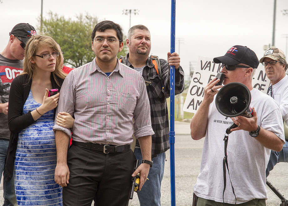 Henry Vichique (center), with his wife, Danielle (left), and CJ Grisham (right), president of Open Carry Texas, attend a rally in  April  at the San Antonio Police Department West Substation. Photo: Alma Hernandez / For The Express-News / San Antonio Express-News