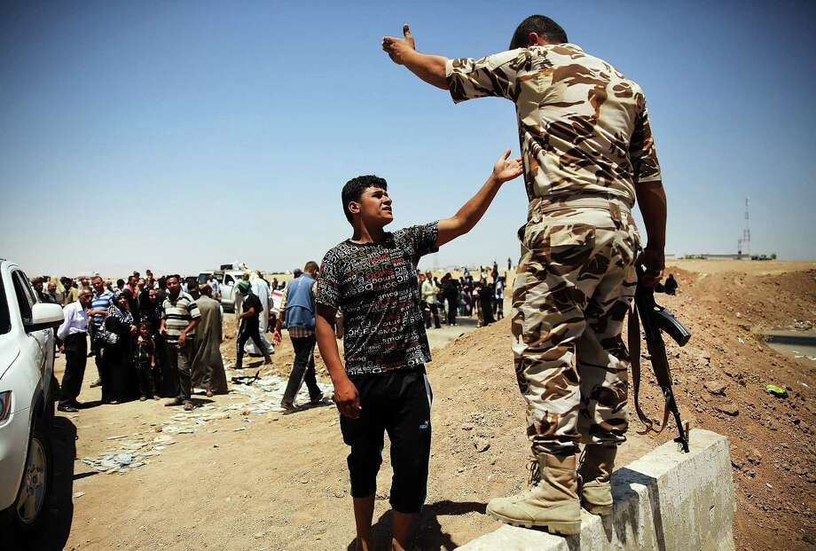 A man argues with a Kurdish soldier as Iraqis who have fled fighting in the cities of Mosul and Tal Afar try to enter a temporary displacement camp. Photo: Spencer Platt / Getty Images / 2014 Getty Images