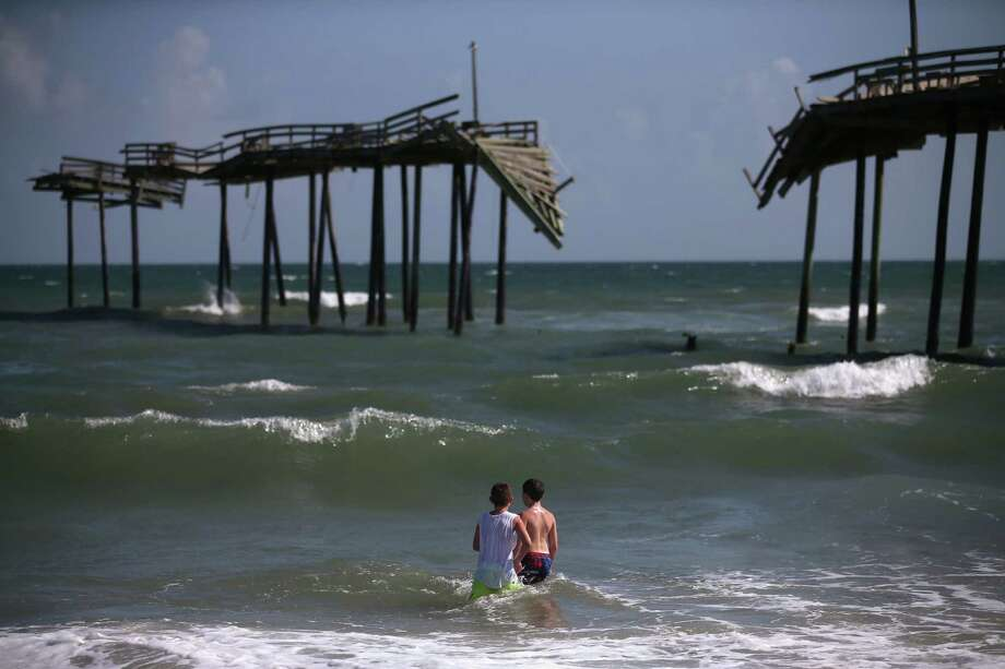 Koby Cooper (left) and Colby Atkins of Charleston, W.Va., play near the old damaged Hatteras Pier in Cape Hatteras, N.C. Photo: Mark Wilson, Getty Images / 2014 Getty Images