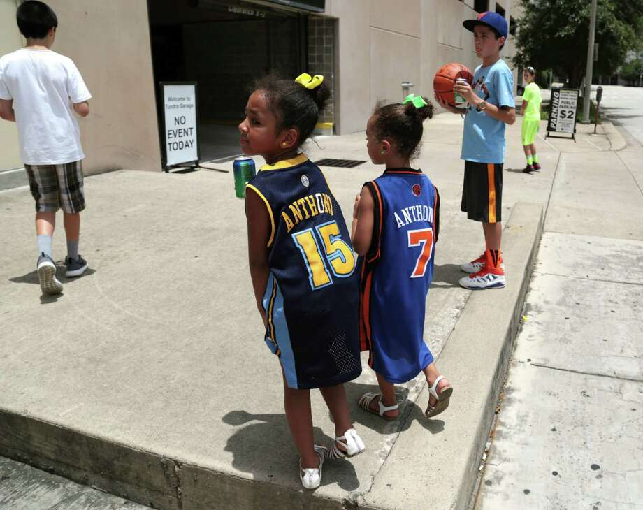 Sisters Alene, left, and Aliyah Contreras are such big fans of Carmelo Anthony that they were hoping to catch a glimpse of him Wednesday outside Toyota Center while decked out in their Nuggets and Knicks versions of his jersey. Photo: Billy Smith II, Staff / © 2014 Houston Chronicle