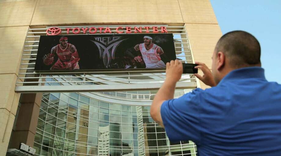 With camera aimed at Toyota Center's marquee, Rockets fan Frank Vasquez shoots what many hope comes to pass - forward Carmelo Anthony in a Rockets jersey. Photo: Billy Smith II, Staff / © 2014 Houston Chronicle