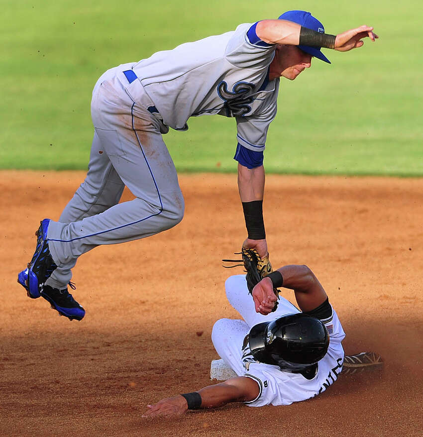 San Antonio Missions baserunner Reymond Fuentes slides safely under Tulsa Drillers shortstop Trevor Story during Texas League action at Wolff Stadium on Wednesday, July 2, 2014.