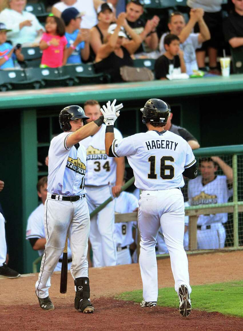 Jason Hagerty of the San Antonio Missions is congratulated by teammate Austin Hedges after hitting a home run against Tulsa during Texas League action at Wolff Stadium on Wednesday, July 2, 2014.