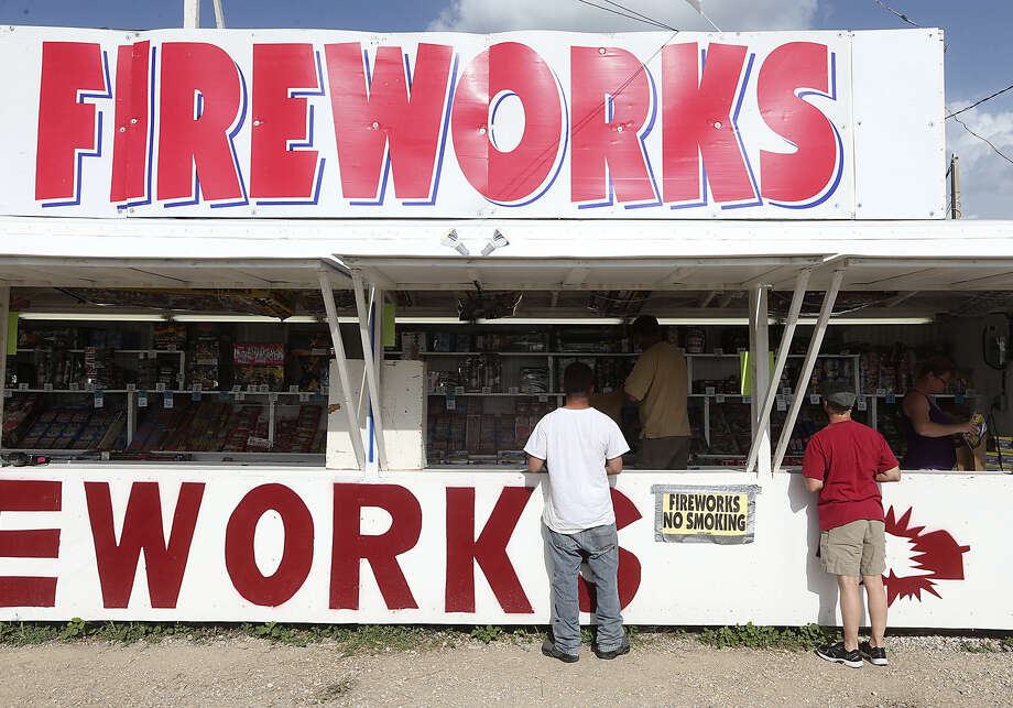 Residents buy fireworks from a stand at U.S. 87 and Triple Tree Street. The stand opened for the holiday on June 24 and will close at midnight Friday. Photo: Jerry Lara, San Antonio Express-News / ©2014 San Antonio Express-News