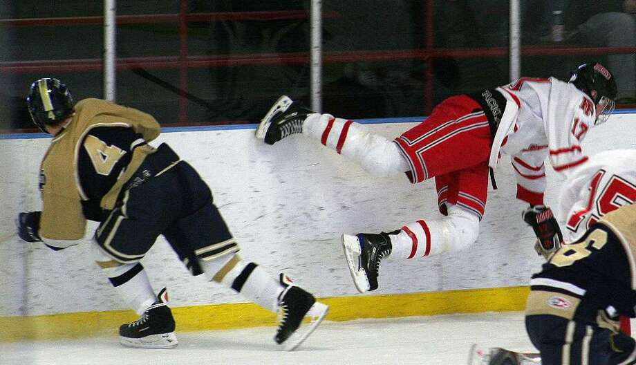 Notre Dame-Fairfield's Tyler Schmarr sends Fairfield Prep's Lucas Dennison airborne in the Jesuits' 5-2 win over the Lancers on Feb. 13 at Wonderland of Ice. Photo: Tim Parry