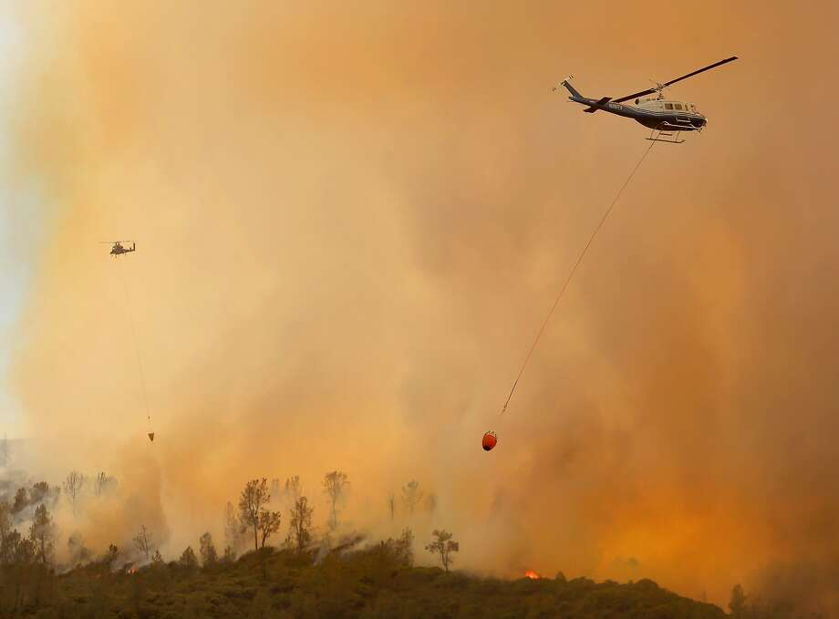 Private hire helicopters make water drops on the Butts Fire above Snell Valley as the afternoon winds kicked up, Wednesday, July 2, 2014, near Middletown, Calif. (AP Photo/Santa Rosa Press Democrat, Kent Porter) Photo: Kent Porter, Associated Press