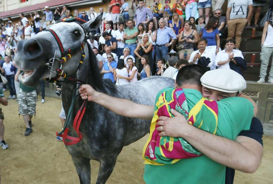 "Supporters of the ""contrada"" (district) Dragon, celebrate their horse after he won the ""Palio"" horse race on July 2, 2014 in Siena. The Palio medieval race is held twice a year in Siena with jockeys riding bareback around a makeshift race course set up in the city's central square. AFP PHOTO/ FABIO MUZZI