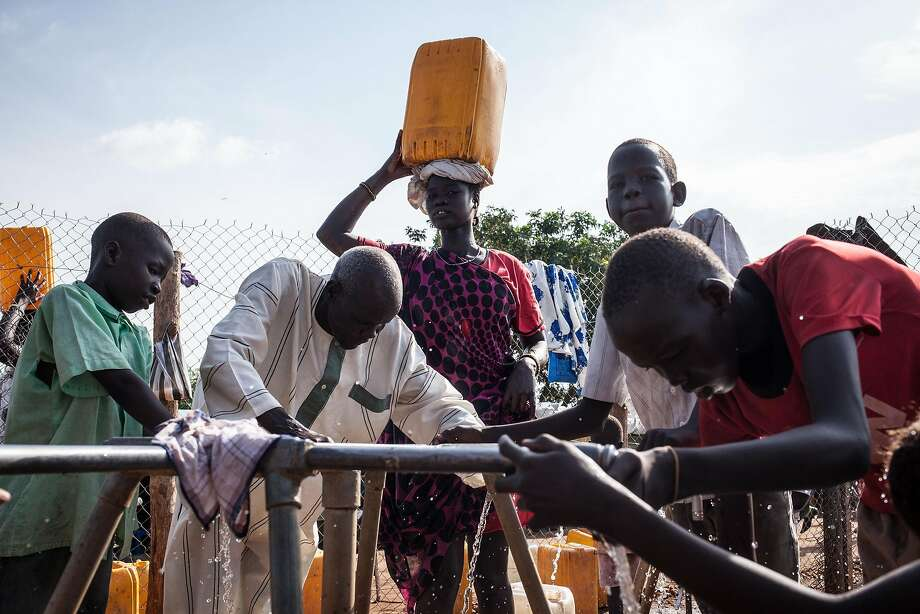 A woman carrying a bucket of water on her head looks on as refugees gather water at the Tomping Internally Displaced Persons (IDP) camp in Juba on July 2, 2014. The United Nations Mission in South Sudan (UNMISS) started to move some refugees from the Tomping IDP camp to the Juba 3 camp in an effort to improve living conditions. Over a million people have been displaced outside of their areas since fighting broke out six months ago, many in overcrowded conditions that are worsening with the early arrival of torrential rains. AFP PHOTO / NICHOLE SOBECKINichole Sobecki/AFP/Getty Images Photo: Nichole Sobecki, AFP/Getty Images