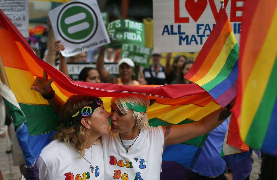 MIAMI, FL - JULY 02:  Barb Lawrence (L) and Kimmy Denny kiss as they stand with others to show their support of the LGBTQ couples who are asking the state of Florida to recognize their marriage at the Miami-Dade Courthouse on July 2, 2014 in Miami, Florida.  Six couples that identify as Lesbian, Gay, Bisexual, Transgender and Queer (LGBTQ) are in court asking that their same-sex marriage be recognized in the state of Florida. (Photo by Joe Raedle/Getty Images) Photo: Joe Raedle, Getty Images