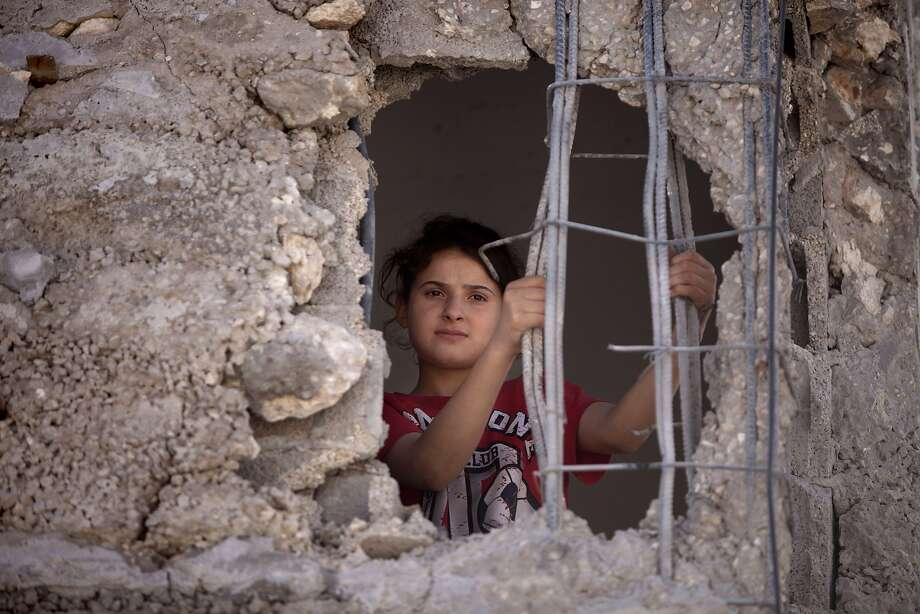 Mai Awad looks out from the damaged family home of Palestinian Ziad Awad in the town of Idna,13 kilometers (8 miles) west of the West Bank city of Hebron, Wednesday, July 2, 2014. Israel demolished on Wednesday the West Bank home of Ziad Awad, who it accuses of having killed an Israeli police officer in April. The move marks a return to a policy abandoned by the military in 2005. Israel sees house demolitions as a deterrent to violence while critics charge it is a form of collective punishment. (AP Photo/Nasser Shiyoukhi) Photo: Majdi Mohammed, Associated Press