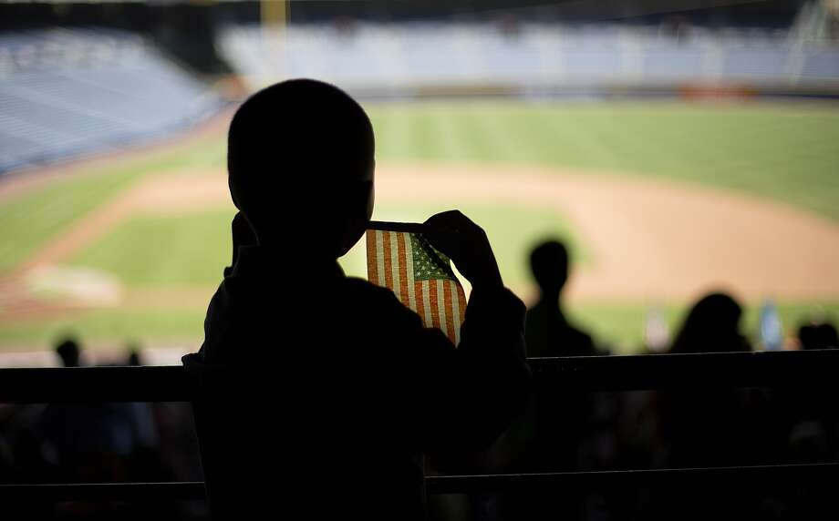 Jensi Francisco, 4, holds an American flag while attending a naturalization ceremony in which his mother, Jennifer Francisco, of the Dominican Republic, became a U.S. citizen at Turner Field, home of the Atlanta Braves baseball team, Wednesday, July 2, 2014, in Atlanta. U.S. Citizenship and Immigration Services welcomed 1,094 new citizens from 81 countries as part of their annual Independence Day celebration marking the nation's 238th birthday this year. (AP Photo/David Goldman) Photo: David Goldman, Associated Press