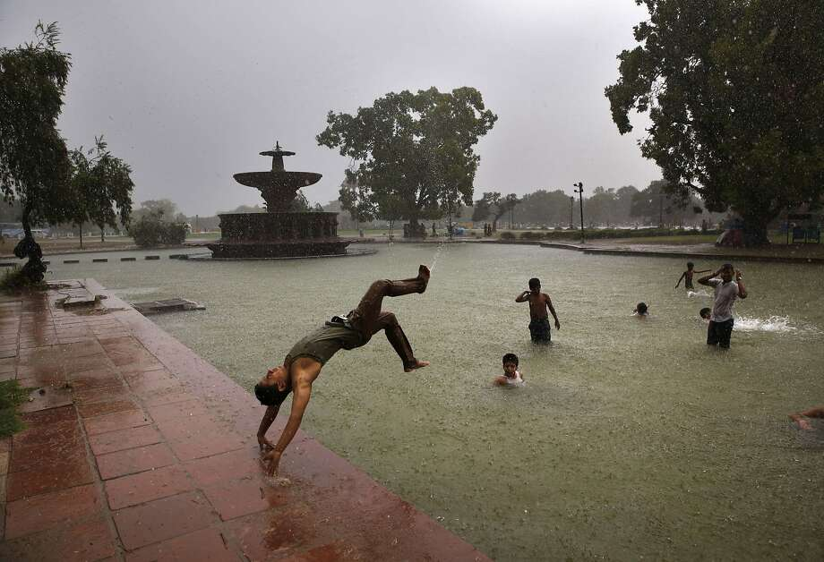 A boy somersaults into a water body as it rains in New Delhi, India, Wednesday, July 2, 2014. According to the weather office, the monsoon rains are expected to arrive at the national capital in a couple of days. (AP Photo/Manish Swarup) Photo: Manish Swarup, Associated Press