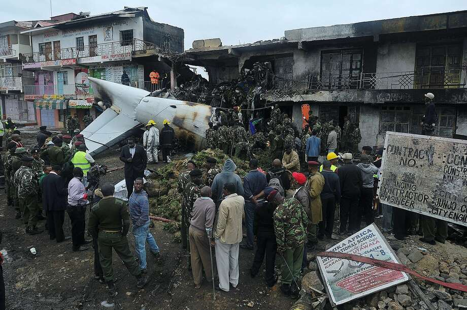 Rescuers and onlookers look at the wreckage of a cargo plane which crashed at a commercial building in a Nairobi susburb shortly after takeoff on July, 2, 2014  from the Kenyan capital's main airport, the busiest in east African. The Fokker 50 cargo airplane crashed with four crew just outside the airport as it took off to ferry khat to neighbouring Somalia. AFP PHOTO/TONY KARUMBATONY KARUMBA/AFP/Getty Images Photo: Tony Karumba, AFP/Getty Images