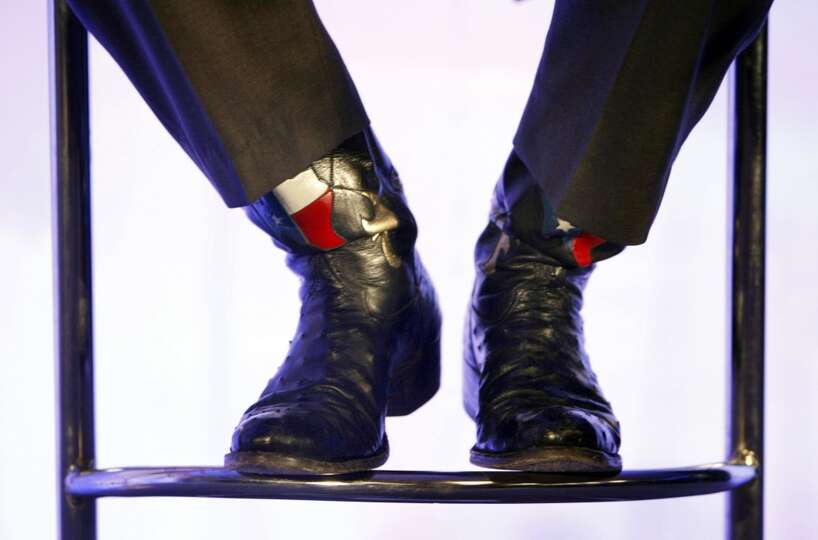 The Western boots of Texas Governor Rick Perry are seen as Republican presidential hopeful, Sen. Joh