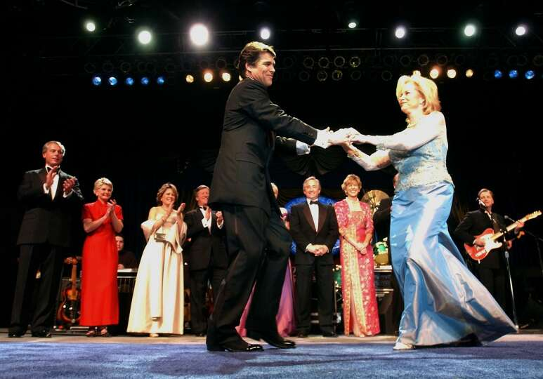 Rick Perry, wearing boots, and his wife Anita dance on stage during the 2003 Inaugural Ball at the A