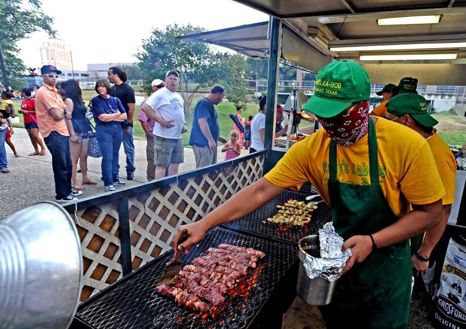 Bat Sebastian, at Rudy's Kabobs hits the grill as a line begins to form during the City of Beaumont Fourth of July Celebration on Thursday, July 4, 2013 at Riverfront Park. Photo taken: Randy Edwards/The Enterprise
